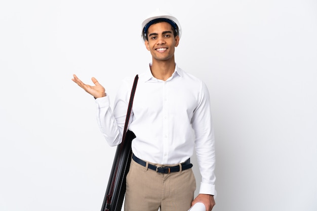 Homme architecte afro-américain avec casque et tenant des plans sur un mur blanc isolé _ tendre les mains sur le côté pour inviter à venir