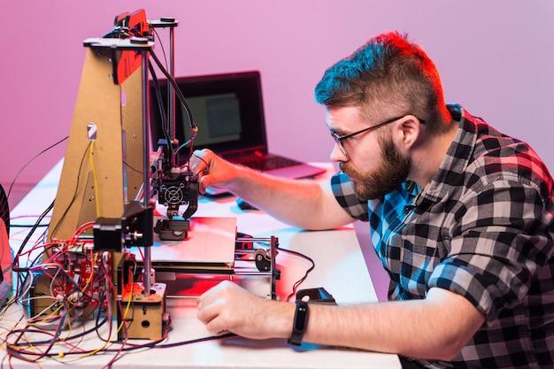 Homme architecte à l'aide d'une imprimante 3d au bureau.