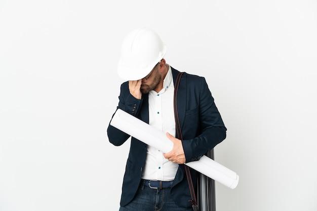 Homme architecte avec casque et tenant des plans isolés sur fond blanc avec une expression fatiguée et malade