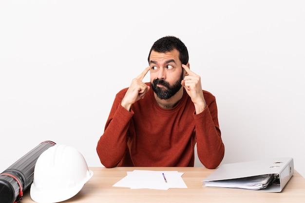 Homme d'architecte caucasien avec barbe dans une table ayant des doutes et de la réflexion.