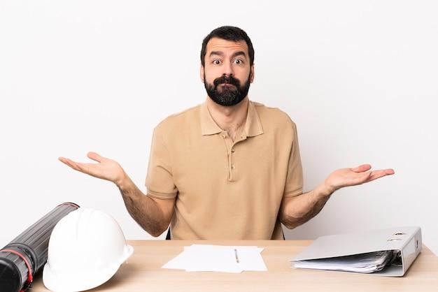 Homme architecte caucasien avec barbe dans une table ayant des doutes tout en levant les mains