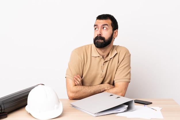 Homme architecte caucasien avec barbe dans une table ayant des doutes tout en levant les yeux