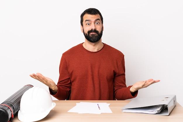 Homme d'architecte caucasien avec barbe dans une table ayant des doutes.