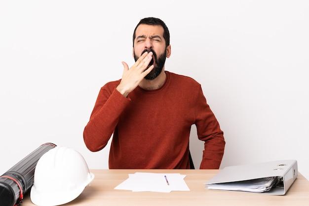 Homme d'architecte caucasien avec barbe dans une table bâillant et couvrant la bouche grande ouverte avec la main.