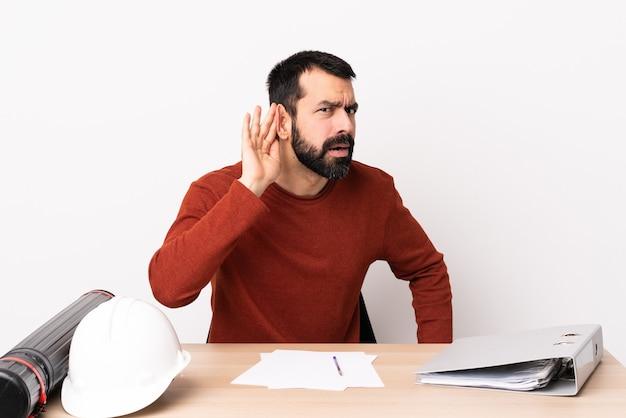 Homme d'architecte caucasien avec barbe dans une table écoutant quelque chose en mettant la main sur l'oreille.