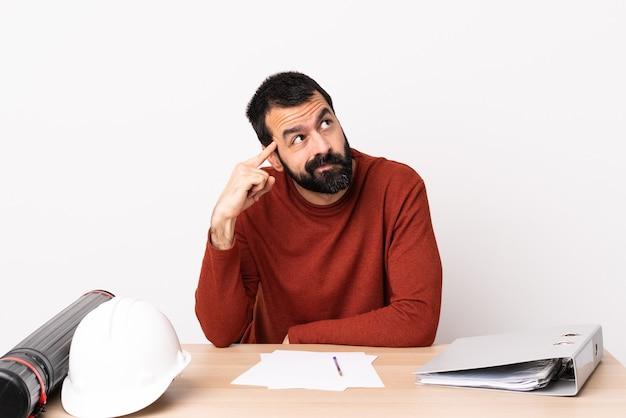 Homme d'architecte caucasien avec barbe dans une table faisant le geste de la folie mettant le doigt sur la tête.