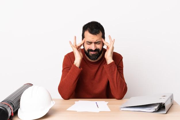 Homme d'architecte caucasien avec barbe dans une table avec des maux de tête.