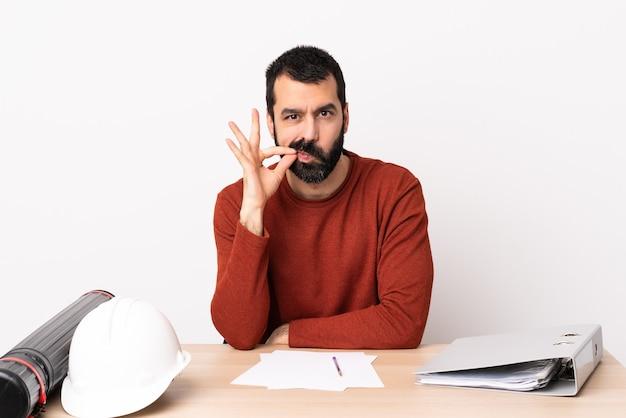 Homme d'architecte caucasien avec barbe dans une table montrant un signe de geste de silence.