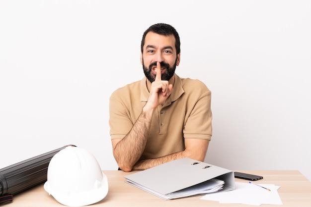 Homme architecte caucasien avec barbe dans une table montrant un signe de silence geste mettant le doigt dans la bouche.