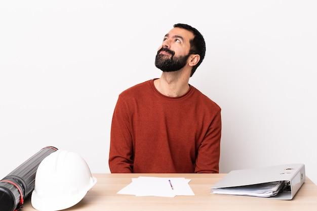 Homme d'architecte caucasien avec barbe dans une table en pensant à une idée tout en levant les yeux.