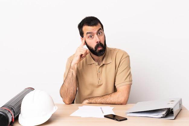 Homme d'architecte caucasien avec barbe dans une table en pensant à une idée.