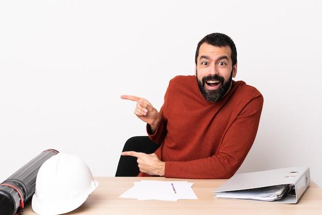 Homme architecte caucasien avec barbe dans une table surpris et pointant du côté.