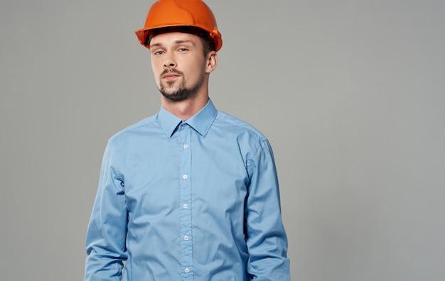 Homme architecte en peinture orange et dans une chemise bleue sur fond gris