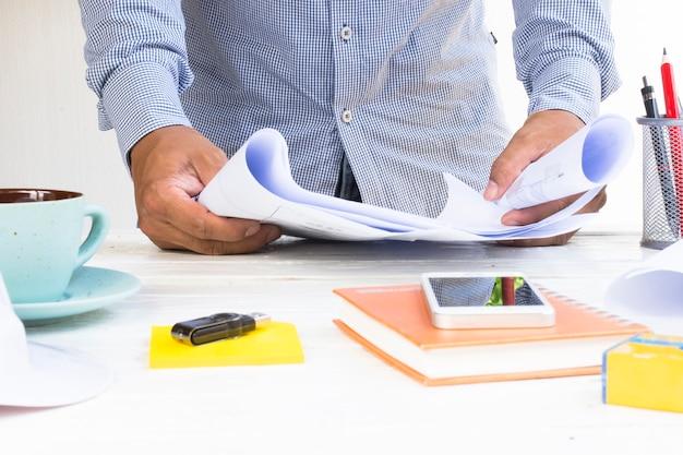 Homme architecte avec plans de maison dans sa main et équipement sur table blanche