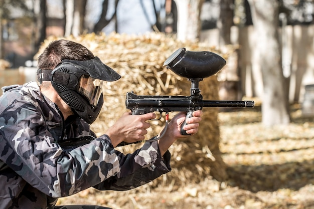 Un homme avec une arme à feu jouant au paintball.