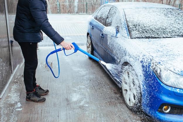 Un homme avec une arme à feu pour appliquer de la mousse sur la voiture. lave-auto en libre-service