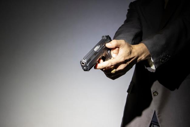 Homme armé tenant arme à feu avec fond sombre