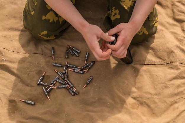 Un homme de l'armée dirige un fusil d'assaut kalachnikov avec 7 62 cartouches. un soldat est assis sur un tissu et charge une arme.