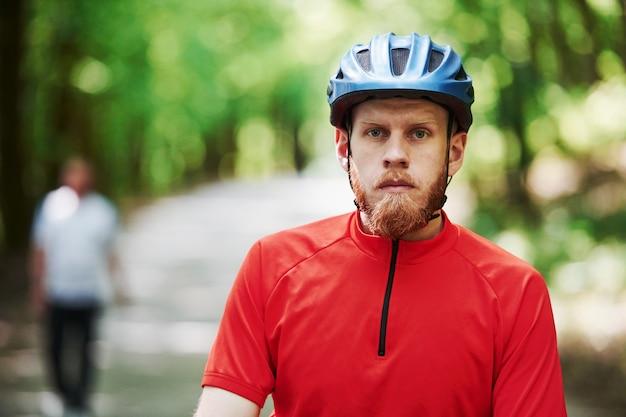Homme en arrière-plan flou. cycliste sur un vélo est sur la route goudronnée dans la forêt à la journée ensoleillée
