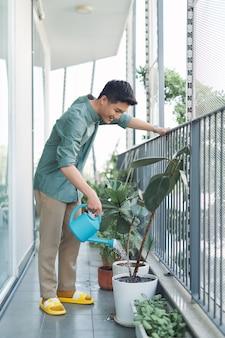 Homme arrosant l'usine dans le récipient sur le jardin de balcon