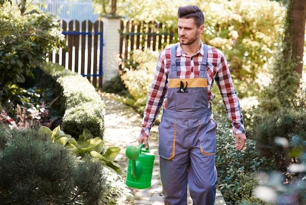 Homme avec arrosoir au jardin