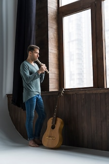 Homme artiste à l'intérieur jouant de la flûte