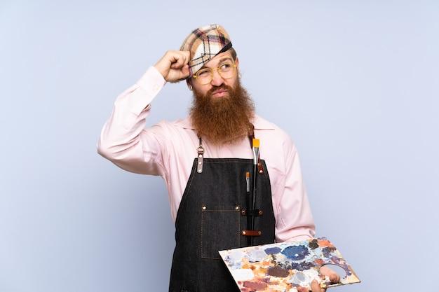 Homme artiste rousse avec une longue barbe tenant une palette sur un mur bleu isolé ayant des doutes et avec une expression du visage confuse