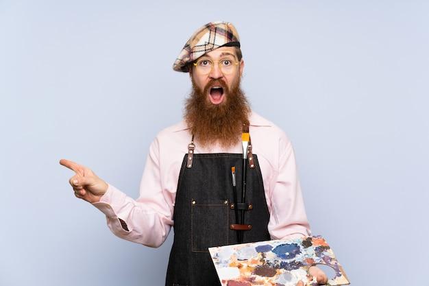Homme artiste rousse avec une longue barbe tenant une palette sur un mur bleu isolé surpris et pointant le doigt sur le côté