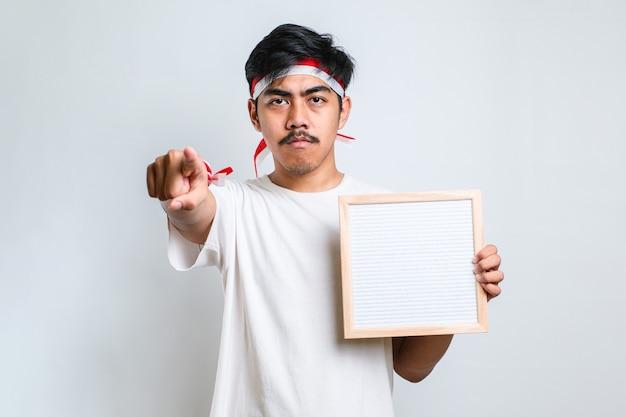 Homme asan portant un bandeau rouge et blanc tenant un tableau vierge pointant du doigt vers la caméra isolée sur fond blanc