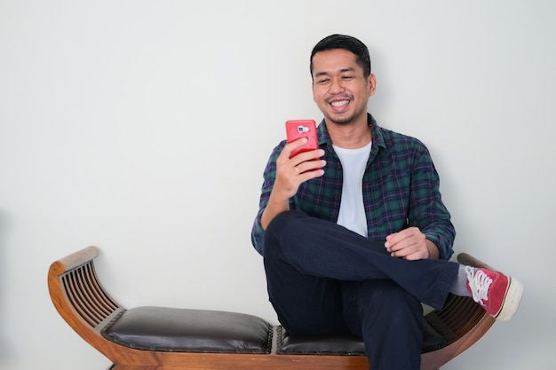 Homme asiatique adulte assis se détendre tout en regardant son téléphone portable