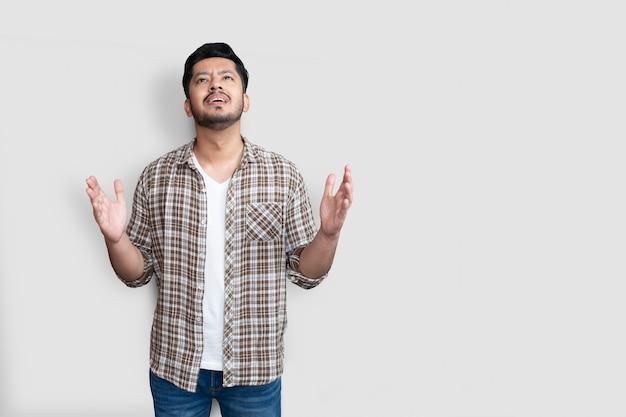 Homme asiatique adulte sur fond isolé criant fou et fou et hurlant avec une expression agressive et les bras levés. concept de frustration.