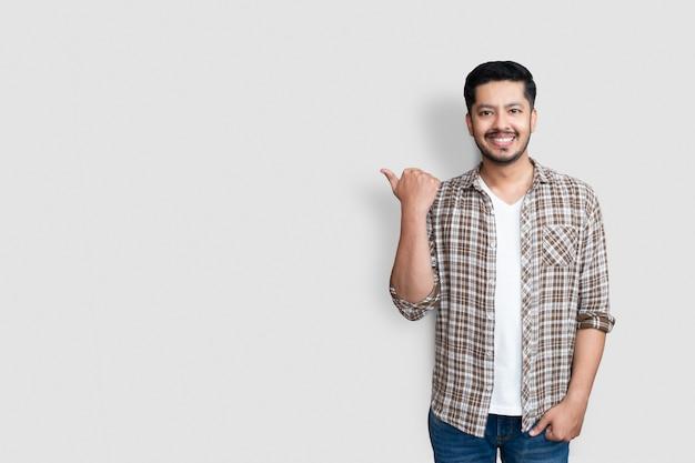 Homme asiatique adulte sur fond isolé souriant avec un visage heureux à la recherche et pointant vers le côté avec le pouce vers le haut.