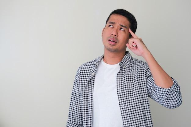 Homme asiatique adulte pointant le doigt sur sa tête et montrant un geste de réflexion