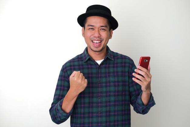 Un homme asiatique adulte serra le poing et montrant de l'excitation tout en tenant un téléphone portable