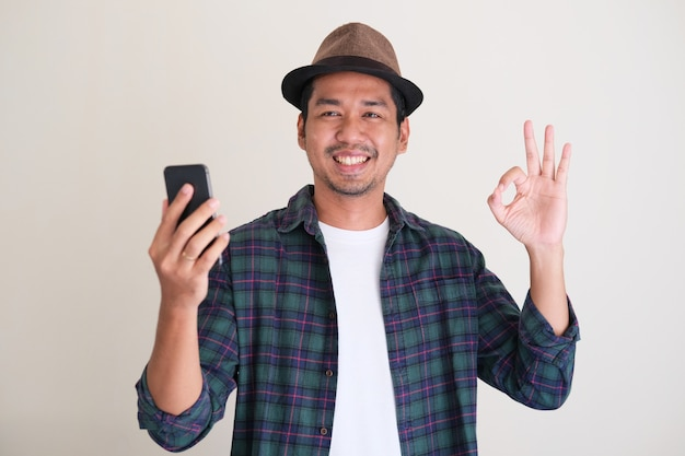 Homme asiatique adulte souriant et donnant un signe du doigt ok tout en tenant un téléphone portable