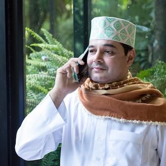 Homme asiatique d'affaires pakistanais en tenue décontractée écrire sur un ordinateur portable à l'aide d'un téléphone mobile intelligent