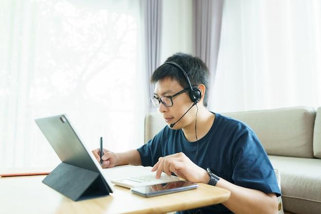 Homme asiatique âgé de 30 à 40 ans à l'aide de tablette, regarder le cours en ligne de cours communiquer