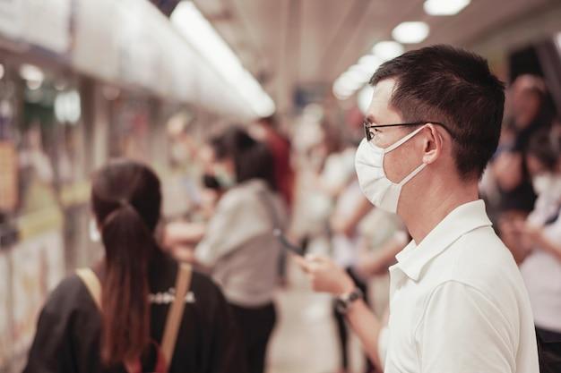 Homme asiatique d'âge moyen portant des lunettes et un masque médical en attente d'un train public avec foule, épidémie de coronavirus de wuhan, pollution de l'air et concept de santé