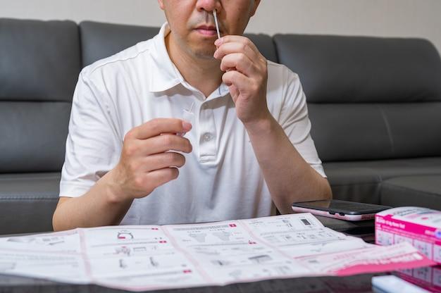 Homme asiatique d'âge moyen testé pour le coronavirus à l'aide de kits d'antigène à domicile covid-19.