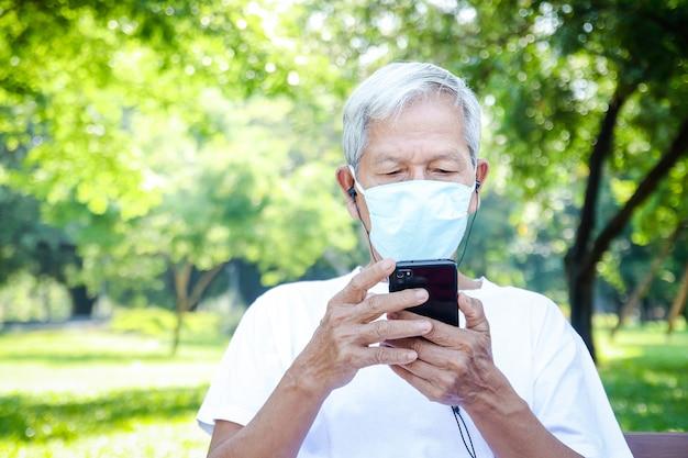 Un homme asiatique âgé portant un masque utilise un smartphone