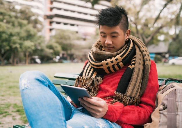 Homme asiatique à l'aide de sa tablette numérique.