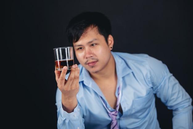 Homme asiatique alcoolique avec un verre de whisky