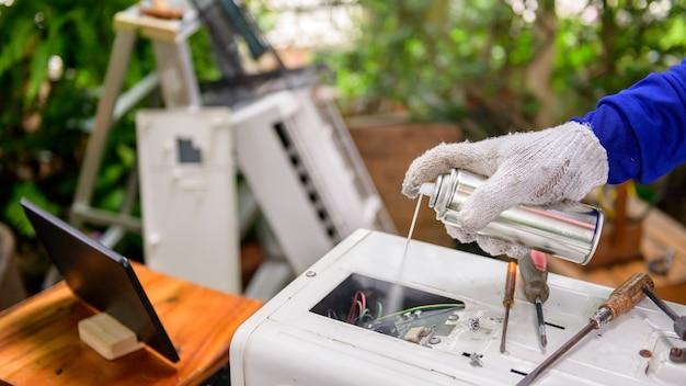 Un homme asiatique apprend en ligne et répare le climatiseur à la maison. distanciation sociale et nouveau mode de vie normal.