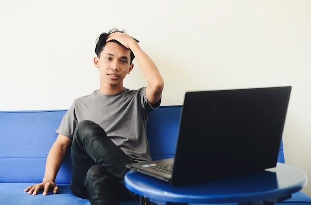Homme asiatique assis sur le canapé expression déçue