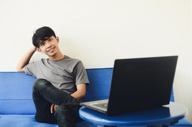 Homme asiatique assis sur le canapé avec une expression joyeuse