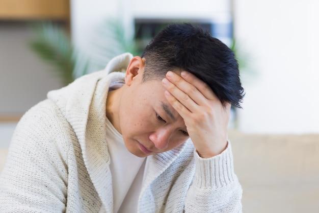 Homme asiatique assis sur un canapé à la maison pensif inquiet des problèmes et de la dépression