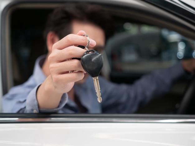 Homme asiatique assis dans une nouvelle voiture et montrant les clés de la voiture. jeune homme séduisant assis automobile salon regardant par la fenêtre ouverte.