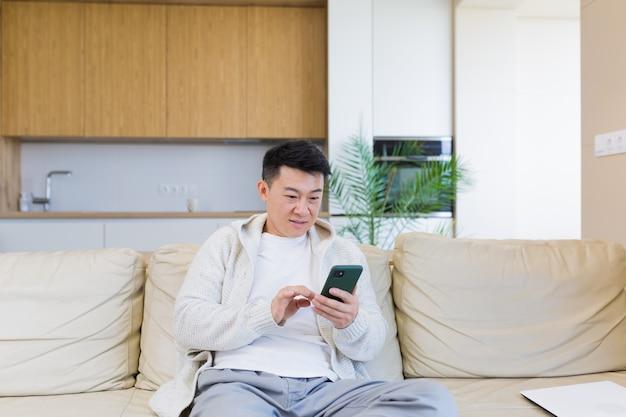 Homme asiatique assis à la maison sur le canapé, utilisant un smartphone, sérieux en tapant un message au téléphone