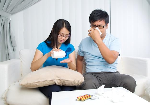 Homme asiatique ayant des médicaments à la maison. femme prend soin de son mari.