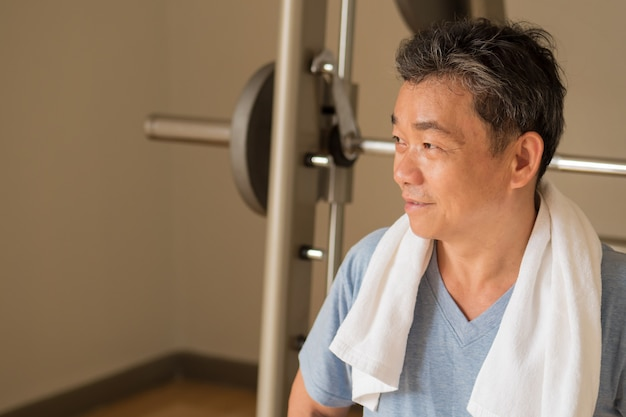 Homme asiatique en bonne santé, heureux, souriant, positif, bien-être senior à la recherche de côté à l'espace vide